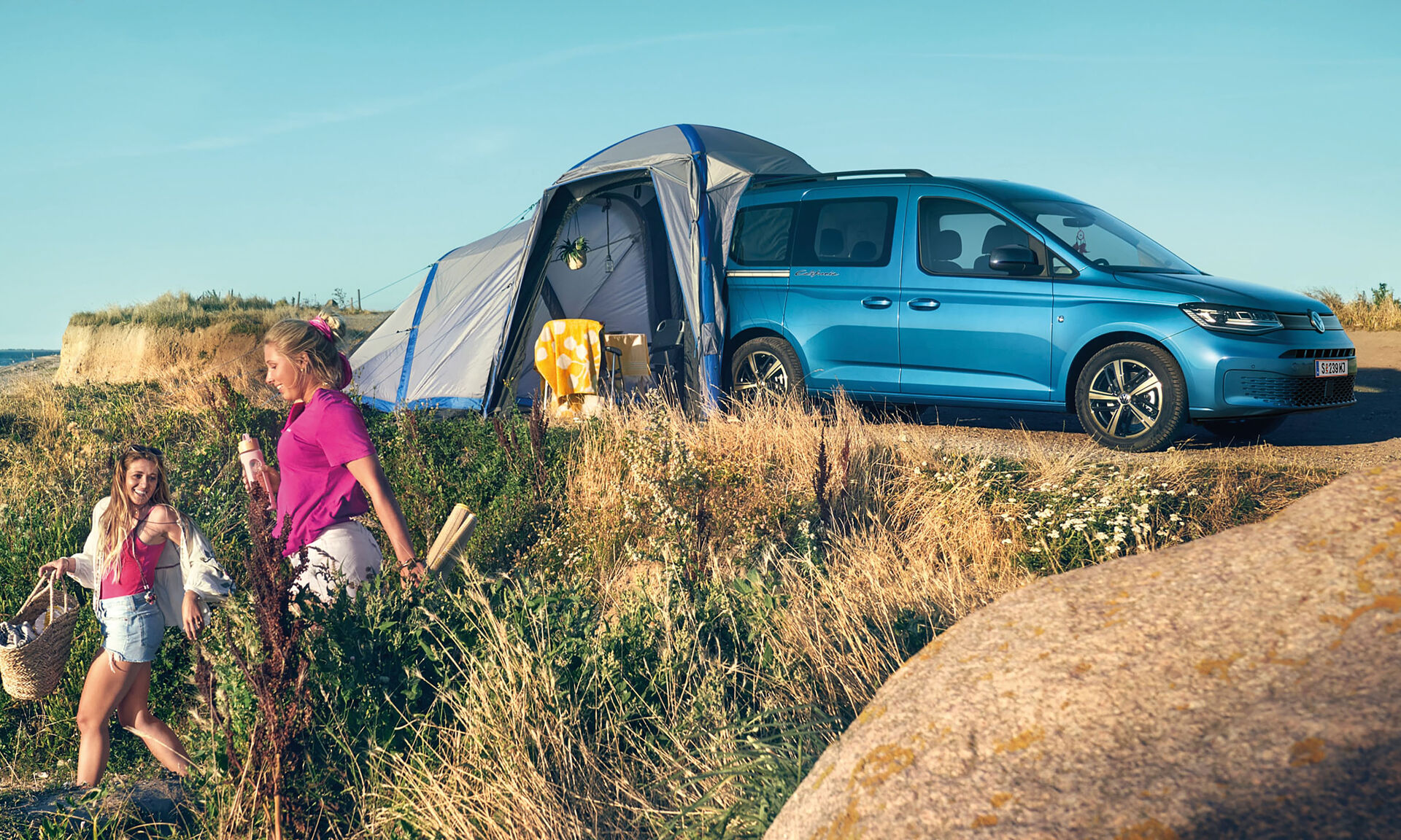 Blauer VW Caddy California mit Zelt am Heck