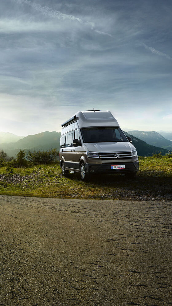 VW Grand California stoji na travniku poleg ceste.